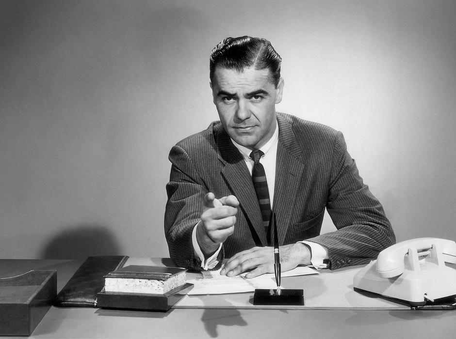 Businessman Sitting At Desk Pointing At Camera