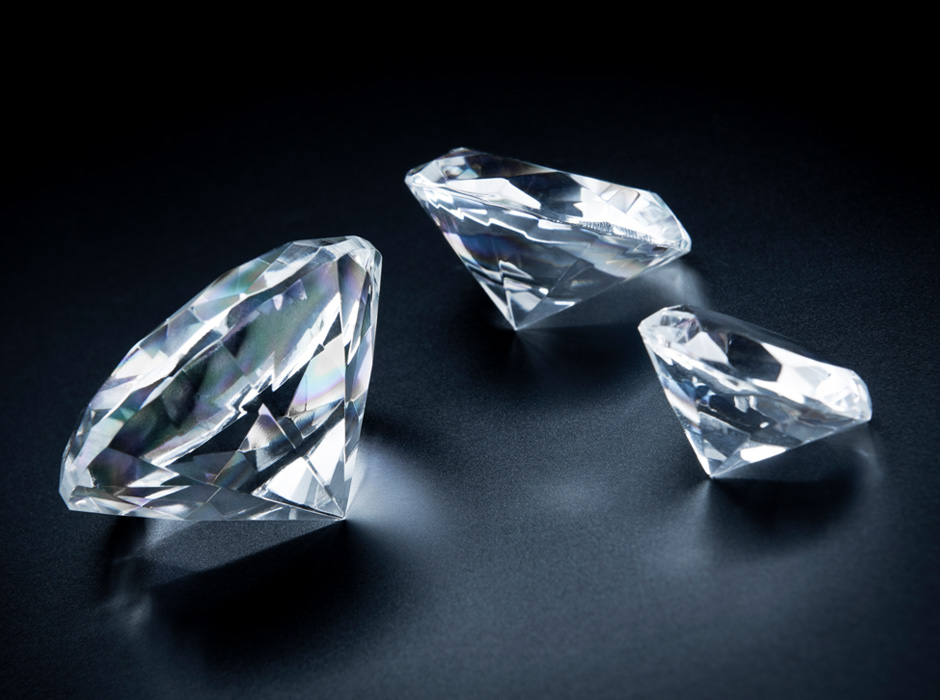 Three Diamonds Sitting On Black Surface